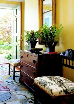 comfortable contemporary upholstery, antiques, and a mix of decorative objects. Pale golden yellow walls pick up color from the custom area rug. Hanging above it is a beautiful gold-framed mirror. Walls striped with light and medium yellow add interest yet remain neutral. A traditional chest is flanked by matching antique chairs.