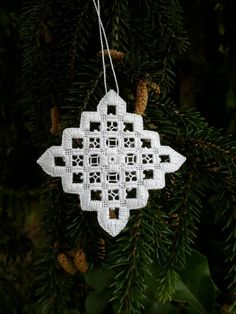 Lacy hand stitched ornament for your Christmas tree or to hang decoratively around your home. The contrast of blocks of satin stitch with the