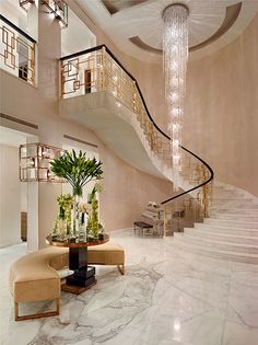 Qater villa: Katharine Pooley Limited (KPL) created a remarkable entrance to the home by installing a bespoke chandelier which cascades through the center of a show-stopping solid brass and glass balustrade.