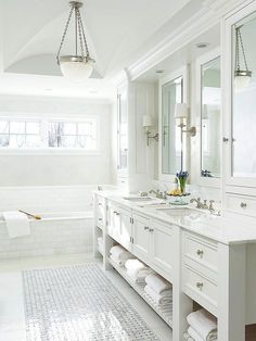 White-on-white isn't for everyone, but you have to agree, the results can be quite stunning. In this elegant bathroom, a mix of sheens and details bring a monochromatic white palette to life. Glossy tilework and mirrored surfaces contrast the matte finish on the cabinetry and walls. Fluted moldings and a groin-vault ceiling lend architectural interest to the sea of white and silver accents introduce glamour. /