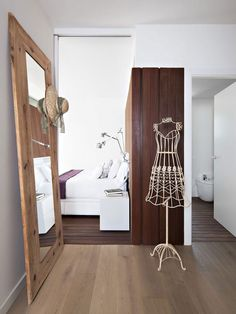 Utiliser l'espace entre la porte de la chambre et celle de la salle de bain (un couloir) comme dressing, un miroir en bout pour allonger l'espace.