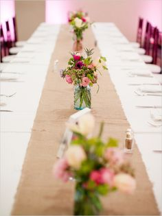 Burlap table runner over white table cloth for wedding tables. mason jars with flowers as table centerpieces along the runner. use pop of accent color in the flower arrangement to add interest to the simple elegant table fabric Wedding Tips, Wedding Vendors, Diy Wedding, Wedding Flowers, Wedding Planning, Wedding Tables, Weddings, Wedding Decor, Dream Wedding
