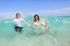 Bride and groom in a wave in the Caribbean Sea trash the dress photo shoot. Fun fun fun in the Mexican sun!  Mexico photographers Del Sol Photography
