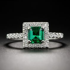 An absolutely gemmy (few come finer) square-cut emerald of African origin, weighing .61 carat, radiates vibrant, rich crystalline green in this recently made (in London) jewel. Superbly rafted in platinum, the enchanting gemstone is framed by small bright white European-cut diamonds that continue along the top of the ring shank.  Splendid! Currently ring size 6 1/2+.