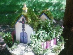 Make from a large planter saucer and prefabbed bird houses, doll house fencing, hot glued moss to the roofs, small plantings, voila!