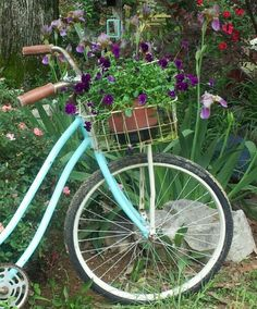 my old blue bike w/ basket and flowers sits at the side of my garden cottage