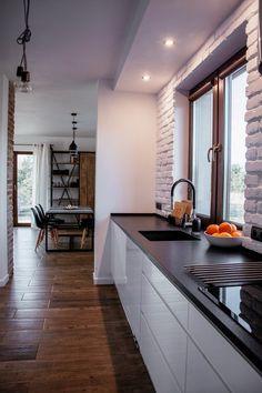 Biała kuchnia z czarnymi dodatkami prezentuje się bardzo elegancko i nowocześnie. Białe cegły w subtelny sposób przełamują klasyczną aranżację, dodając wnętrzu przytulności i charakteru.