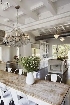 Rustic farmhouse style white and reclaimed wood, crystal chandelier, and airy…