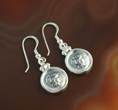 """""""The Strength of Athena"""" are silver earrings with ancient coins representing the fearless goddess Athena, an archetype of the brave woman, boldly striding across life, whose greatest strength is her outstanding intelligence."""