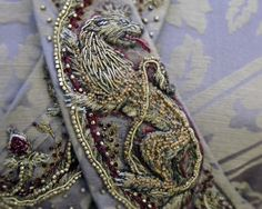 Sansa's wedding dress, embroidered by Michelle Carragher. The dress symbolically tells Sansa's story, beginning with the Tully fish and Stark direwolf entwined at the lower back, and slowly becoming dominated by the Lannister lions towards the front. The colours as still Sansa's, but the increasing amount of red in the designs symbolises the growing Lannister influence over her.