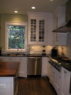 White kitchen with honed granite and mahogany, White cabinets honed absolute black granite perimeter counters mahogany island countertop.