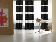 A grommet heading, rings inserted into the top of the curtain fabric, is a contemporary and clean solution for hanging drapes. Make a bold statement with black and white stripes, like the Horizon in Shantung panels from Wildcat Territory. Photo Courtesy of Wildcat Territory.