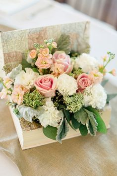 Pink and white flowers potted inside vintage book for travel themed wedding centerpiece | Photo: Brooke Images