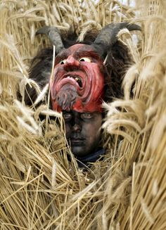 young man in a bizarre straw outfit wears a devil mask for the traditional Buttnmandl run, to shout and make noise on cowbells to frighten people in the village of Bischofswiesen, Germany. (AP)