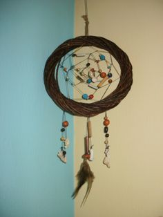 Dreamcatcher of wood, colored waxed thread, beads, shells, and feathers.