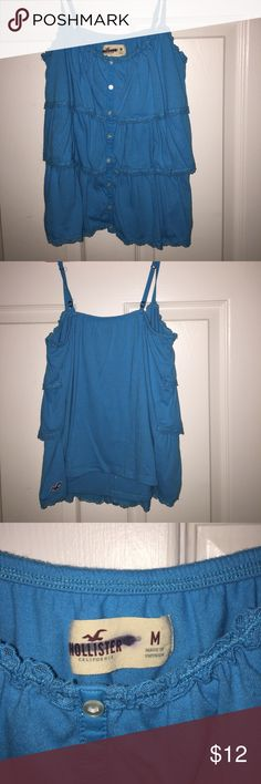 Hollister Tank Top Blue ruffled tank top in a size Medium. Logo is crossed out because I believe i purchased this originally at TJ Maxx. Tank is in great condition. Hollister Tops Tank Tops