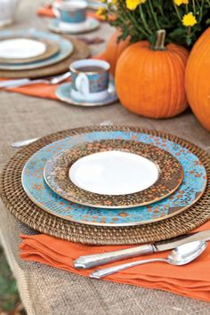 I love these plates. Where can I get them? I also love the pumpkin centerpiece. Words: Pumpkins, teal, orange, plates, dinner, silverware, cups, brown, autumn, fall.