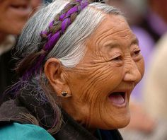 A 70-year-old Tibetan woman is laughing for the buffoon in opera, photo taken on August 11, Xinhua