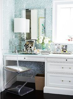 Stunning blue and white wallpaper behind a classic white vanity, decked out with a vintage desk lamp and silver trays.