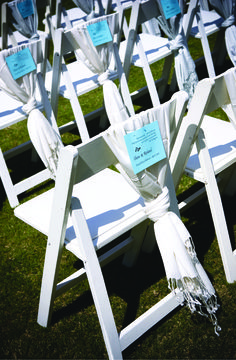 The night before the wedding, the weather turned unseasonably cold, so the bride bought 140 white pashminas for all the guests and draped them over the ceremony chairs.