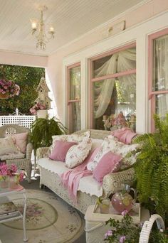 This pink-accented front porch has a shabby chic feel, with wicker furniture and floral accent pillows. The pink and green floral Aubusson rug with an oval medallion brings a sense of indoor comfort to this outdoor space, adding warmth and charm. A vintage chandelier completes the look, and vibrant ferns and potted pink flowers give the design a lush feel. Via Susan's Daily Dose.
