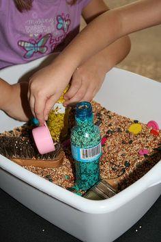 bird seed sensory bin - add bottles to fill.
