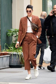 The Keeping Up With The Kardashians star - who had on a burgundy and gold pinstriped blazer with matching slacks - also wore a Louis Vuitton fanny pack crossbod