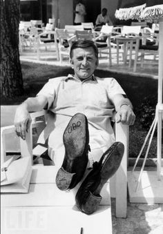 """Kirk Douglas lets his feet do the talking on May 9, 1966. The word """"ciao"""" (""""hello"""" or """"goodbye"""" in Italian) is written on the sole of his shoe. Photo: RDA/Getty Images, May 09, 1966"""
