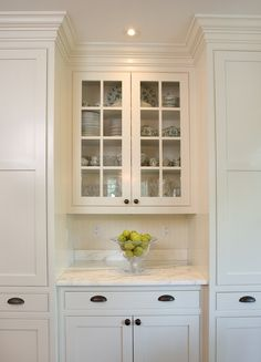 White shaker kitchen cabinets, black pulls, marble counters, glass paneled cabinet