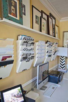Detalle de escritorio con repisa larga donde van cuadros apoyados a la pared y sobres organizadores, también sobre la pared, para guardar papeles.