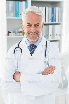 Portrait of a smiling confident male doctor standing with arms crossed at medical office - Stock Photo - Images