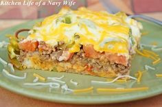 John Wayne Layered Casserole - Packed with great hearty flavors and ingredients like ground beef, biscuit mix, pepper and onion and then topped with a delicious mixture of sour cream, mayo and Cheddar cheese, this is one of those beef casserole recipes that's nearly impossible to resist.