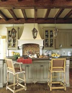 Antiqued Kitchen    With old waxed ceiling beams, pale honey wall plaster, and French and Italian antiques, a new kitchen takes on the mellow glow of age. Design by Fern Santini.