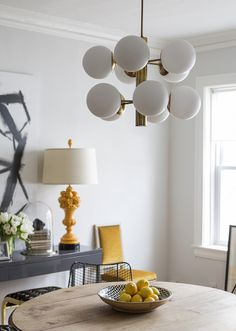 A midcentury globe light fixture hangs above a hand-carved 19th-century French oak table in Matt Carollo's dining room. | Lonny