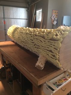 Back of large fake log made from cardboard and spray foam