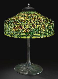 "TIFFANY STUDIOS  A RARE ""BLACK-EYED SUSAN"" TABLE LAMP    with a ""Tree Trunk"" base    shade impressed TIFFANY STUDIOS NEW YORK 1518-1  base impressed TIFFANY STUDIOS/NEW YORK/553  leaded glass and patinated bronze  33 7/8 in. (86 cm) high  25 3/8 in. (64.5 cm) diameter of shade  circa 1910"