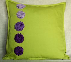 Green pillow with crochet violet flowers