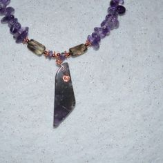 Auralite 23 necklace beaded by Dee with Amethyst, copper and citrine natural beads.  Auralie 23 carries 35 elements, and in each crystal, there is at least 17 of these combined. There is 23 minerals in its matrix, which includes:  Titanite, Cocoxenite,Lepidocrosite,Malachite,Hematite,Magnetite,Pyrolusite, Gold,Silver,Platinum,Nickel,Copper,Iron,Limonite,Shpalente,Covelite,Chalcopyrite, Gilaltie, Epidote,Bornite & Rutile.