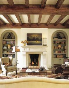 """In the family room, off the kitchen, Santini added antique pine ceiling beams and raised the height of the arched bookshelves. A Cameron Collection sofa upholstered in Great Plains Velvet Etching sits in front of a custom coffee table by Abode. """"I love those big leather Rose Tarlow chairs. They're so comfortable,"""" says Santini. The antique iron floor lamp with an unusual cattails detail is from Watkins Culver."""