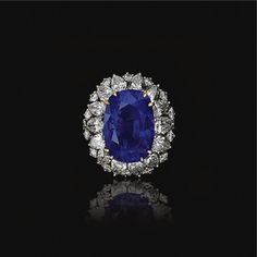 SAPPHIRE AND DIAMOND RING, OSCAR HEYMAN & BROTHERS Claw-set with a cushion-shaped sapphire weighing 17.84 carats, within a line of pear-shaped diamonds, further decorated with brilliant-cut stones, mounted in yellow gold and platinum, numbered.