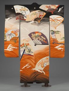Kimono (furisode), Japanese, Taishô or Shôwa era, late 1920s–1930s, Center back: 170.2 cm (67 in.), Long-sleeved robe (furisode) with overall, large-scale design of fan shapes decorated with auspicious motifs in blue, green, orange floating on a black, orange and white ground of swirling waves. Five crests with three heart-shaped leaves turned inward (symbol of shogun families).