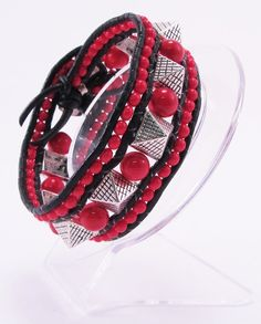 Another really cool rocker 3 row cuff! This one has black leather, silver tone metal pyramids, red glass beads and a silver tone acrylic button. The spiked pyramids stand out approximately 10mm. The red beads in between are 8mm.  This cuff is unisex and can be worn by anyone with an 7 inch wrist! $35.00