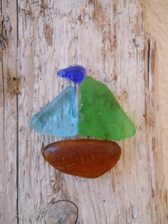 Sea glass sail boat on driftwood.