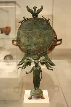 A Magnificent and Important Greek Early Classical Bronze Mirror, the Handle in the Form of a Woman Surmounting Base with Three Bovine Feet  Bronze, Early Classical, ca. 460-450 B.C.E.