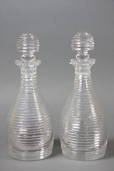 A pair of late Georgian Step-cut glass decanters early, 19th century, each with a broad octagonal pouring lip above a waisted neck and ovoid body, step-cut throughout, with conforming stoppers. Height ; 28 cm