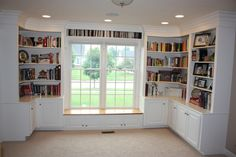 Wrap around bookcases with cabinets and a window seat. The cabinets' corners create a 90* angle while the shelves' corners are at a 45* angle.