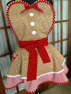 Adorable gingerbread man apron made with warm brown fabric with happy little gingerbread men and candy canes.