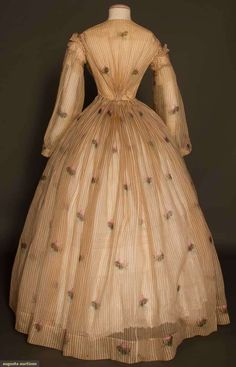 Ca.1860 voile dress printed with a brown check and floral motifs. Bodice shirred at CF and CB; ruched bias trim to scye and cuff; skirt waist gauged. Augusta Auctions.