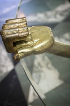 Kelly Wearstler May 2013 Issue - A gilded hand holding the edge of a glass tabletop