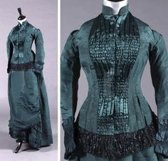 Two-piece, petrol-blue silk faille gown, Limerick Warehouse Co., Limerick, late 1880s. Bodice front adorned with ruched and gathered satin panels, with fringing on the hem. Skirt has goffered satin pleats at the hem and ruched satin front skirt panel. Kerry Taylor Auctions